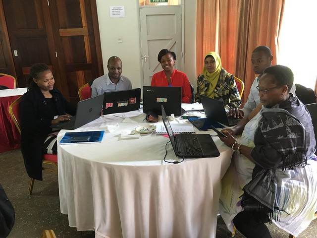 Here is a picture of a group of kenya librarians sitting in circle using computers